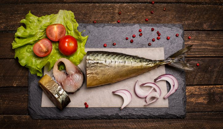Food background. Smoked mackerel background. Smoked mackerel on slate board, top view.  Smoked fish with onion, tomato and pepper.